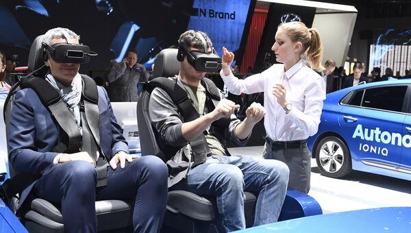 Посетители в очках виртуальной реальности на Женевском международном автосалоне