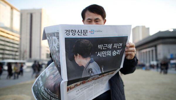Мужчина читает газету с новостью об импичменте Пак Кын Хе, Сеул. 10 марта 2017 год