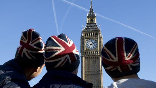 Мужчины в шапках с флагом Великобритании у здания парламента в Лондоне. Архивное фото