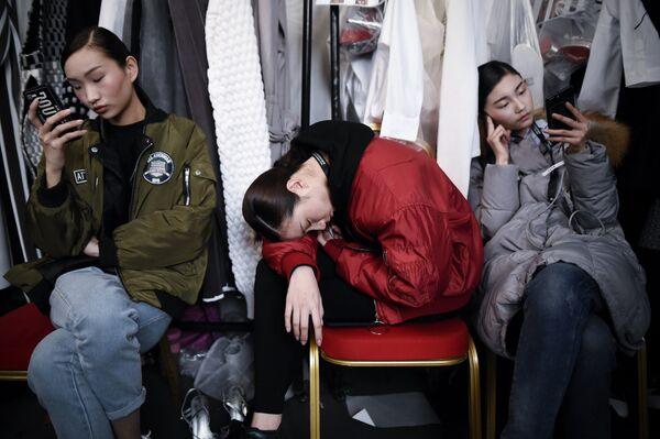 Модели отдыхают за кулисами на Неделе моды в Пекине