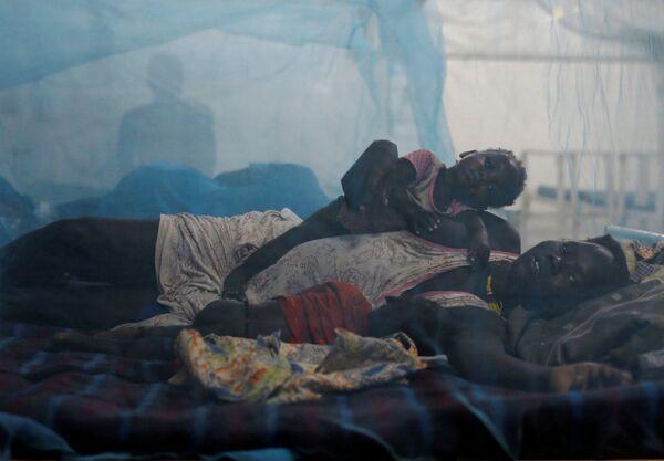 Женщина лежит в постели вместе со своими детьми в госпитале в Южном Судане