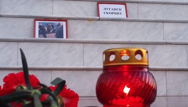 Цветы и свечи в память о погибших во время взрыва у станции Сенная площадь в Луганске