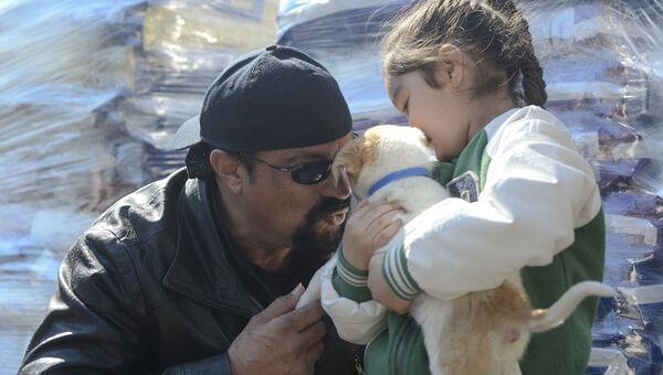 Американский актер Стивен Сигал рассматривает семимесячного щенка, взятого в одном из приютов Бухареста