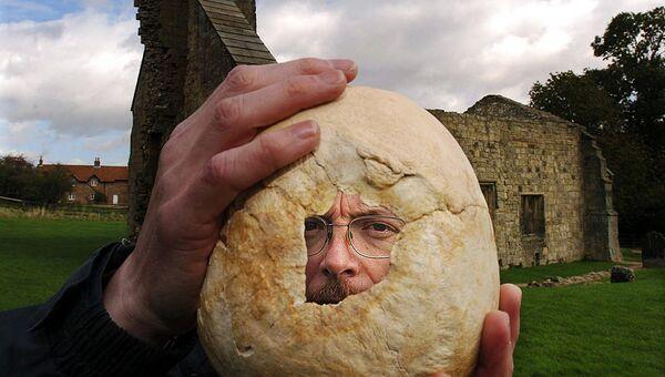 Археолог Саймон Мэйс из университета Саутгемптона держит череп, найденный при раскопках в Уорэм-Перси, Великобритания