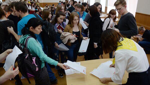 Участники ежегодной акции по проверке грамотности Тотальный диктант — 2017 сдают заполненные бланки в аудитории Омского государственного университета им. Достоевского