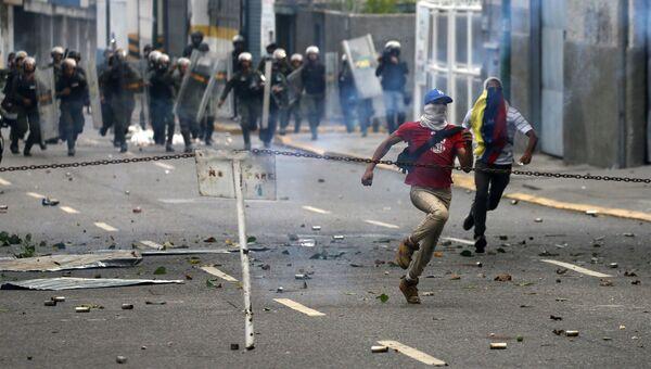Демонстранты убегают во время протестов в Каракасе, Венесуэла. 11 апреля 2017