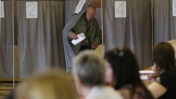 Мужчина выходит из кабинки во время голосования на выборах мэра города Омска. Архивное фото
