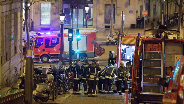 Сотрудники пожарной службы неподалеку от места перестрелки в Париже. Один полицейский погиб, еще один ранен при перестрелке в районе Елисейских полей в Париже