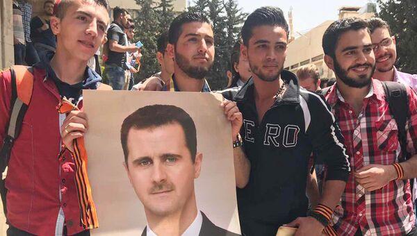 Студенты с портретом президента Сирии Башара Асада во время акции Георгиевская ленточка на территории Дамасского государственного университета