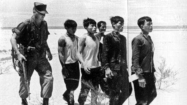 Американский офицер конвоирует пленных патриотов. Репродукция снимка из газеты Комсомольская правда от 30 сентября 1965 года