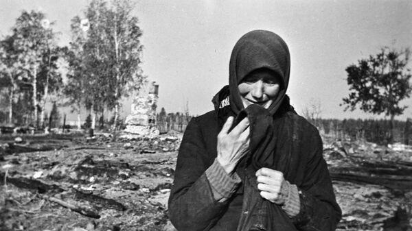 Женщина плачет на развалинах родного села, сожженного фашистами во время Великой Отечественной войны