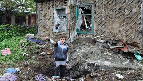 Подросток демонстрирует повреждения жилого дома, полученные в результате обстрела Куйбышевского района Донецка. 10 мая 2017