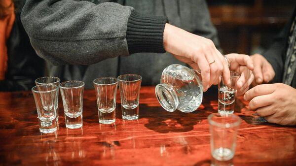 Посетитель разливает водку в баре. Архивное фото