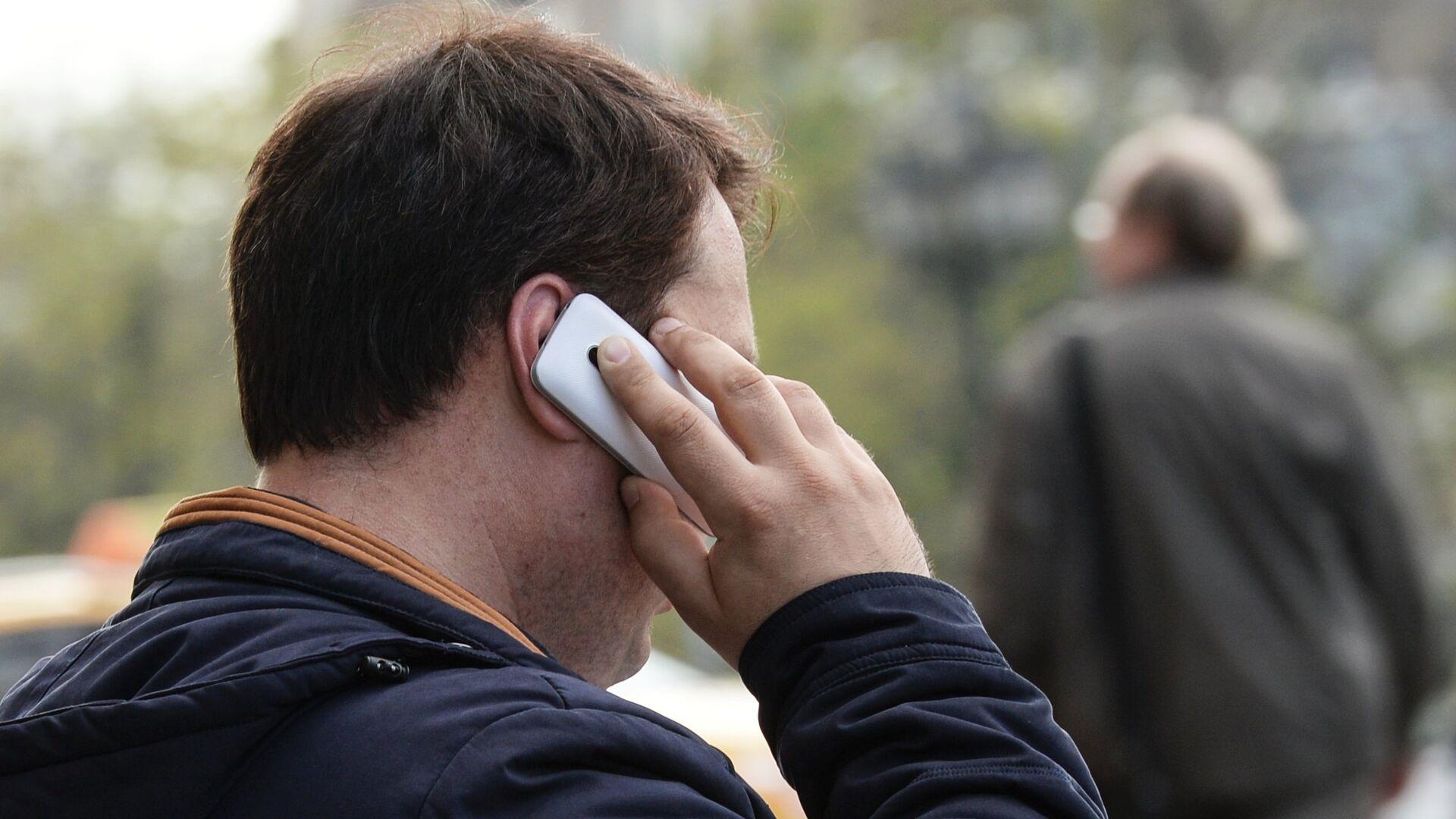 Мужчина говорит по телефону на улице Москвы. - РИА Новости, 1920, 17.09.2020