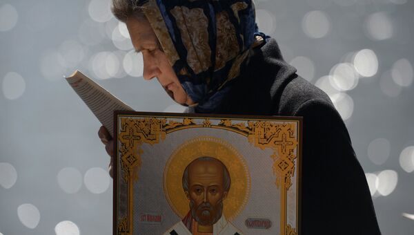 Верующая стоит в очереди к храму Христа Спасителя, где находится ковчег с мощами святителя Николая Чудотворца