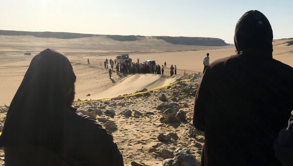Монахи смотрят на место нападения боевиков на группу коптских христиан в Минья