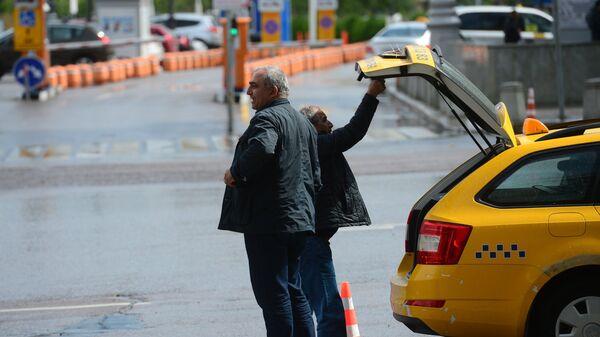Мужчины у автомобиля такси в Москве