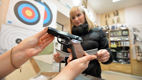 Покупательница рассматривает образцы оружия. Архивное фото