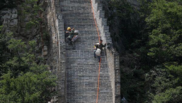 Рабочие несут инструменты для реконструкции Великой Китайской стены