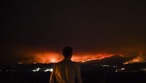 Человек на обочине дороги наблюдает за пожаром в Ансьяо, Лейрия, в Португалии. 18 июня 2017