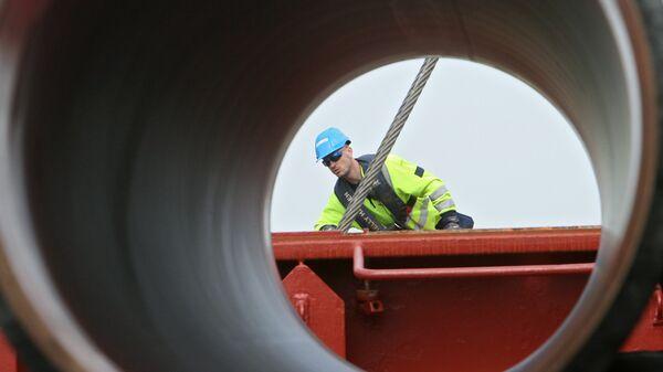 Рабочие подготовливают трубы для строящегося газопровода Северный поток к погрузке на судно доставки. Архивное фото