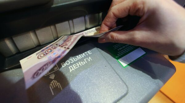 Женщина получает наличные деньги из банкомата. Архивное фото