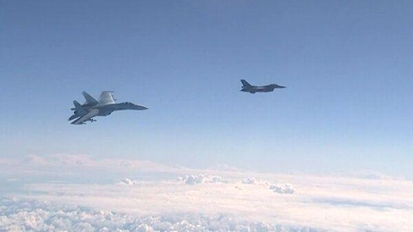 Истребитель НАТО F-16 и российский истребитель Су-27 над водами Балтики. Архивное фото