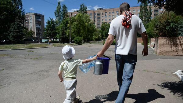 Местные жители с ведрами и канистрами идут к месту подвоза питьевой воды