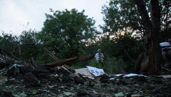 Местный житель стоит у воронки от снаряда во дворе соседского дома. Архивное фото