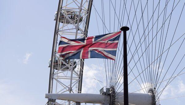Флаг на фоне аттракциона Лондонский глаз в Лондоне. Архивное фото