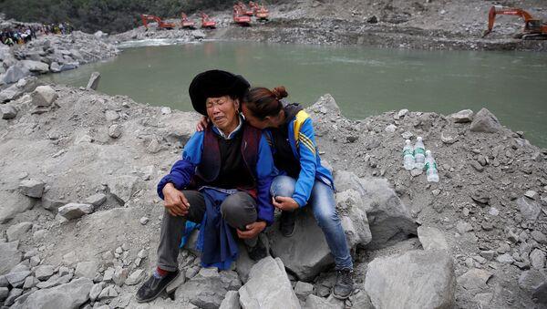 Родственники жертв пострадавших от оползня в деревне Синьмо округа Мао провинции Сычуань, Китай. 26 июня 2017