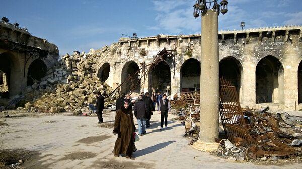 Жители Алеппо во дворе старейшей Мечети Омейядов, разрушенной в результате боевых действий. Архивное фото