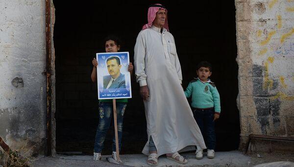 Жители населенного пункта Каукаб в Сирии с портретом Башара Асада. Архивное фото