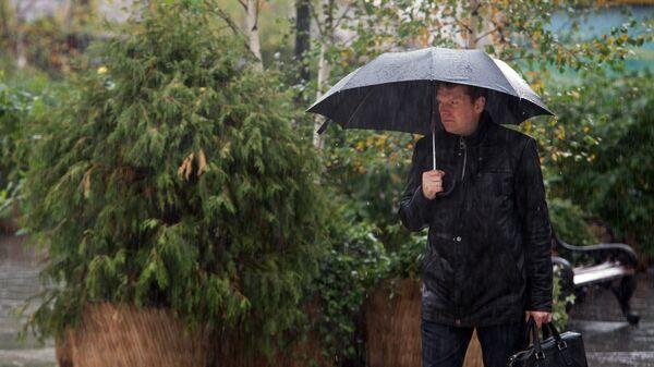 Мужчина с зонтом на улице Кузнецкий мост в Москве во время дождя