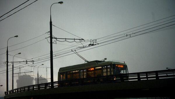 Троллейбус едет по эстакаде во время дождя в Москве. Архивное фото