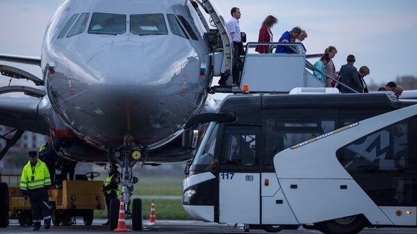 Пассажиры спускаются по трапу с борта самолета