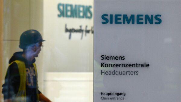 Рабочий у входа в штаб-квартиру компании Siemens в Мюнхене. Архивное фото