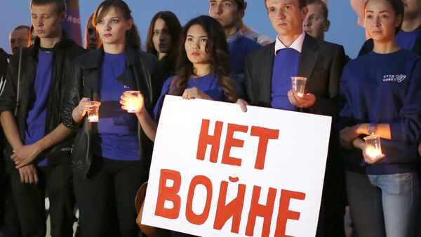 Молодые люди с плакатом Нет войне. Архивное фото