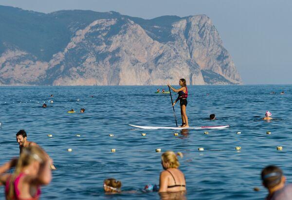 Девушка занимается SUP серфингом в акватории Яшмового пляжа у мыса Фиолент в Севастополе