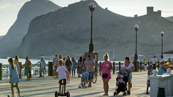 Отдыхающие прогуливаются по набережной в Судаке