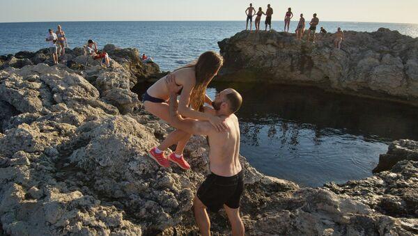 Отдыхающие у природного бассейна Чаша любви на мысе Тарханкут в Крыму