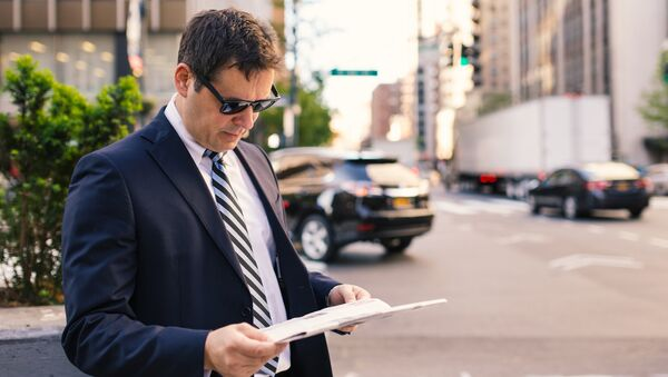 Мужчина читающий газету на Манхеттене. Архивное фото