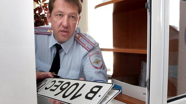 Сотрудник ГИБДД выдает автомобильные номера