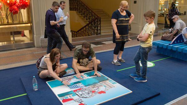 Посетители на выставке, посвященной строящемуся мосту через Керченский пролив, в московском ГУМе на Красной площади. 27 июля 2017
