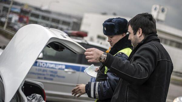Сотрудник ГИБДД проверяет багажник автомобиля водителя в рамках рейда скрытых патрулей ДПС в Москве