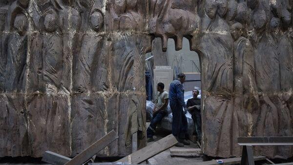 Рабочие готовятся закрепить элементы конструкции монумента Стена скорби перед началом его транспортировки к месту установки в Москве