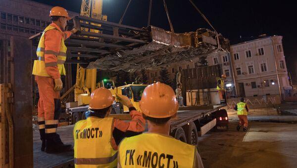 Рабочие выгружают элементы конструкции монумента Стена скорби в месте его установки на пересечении проспекта Академика Сахарова и Садового кольца