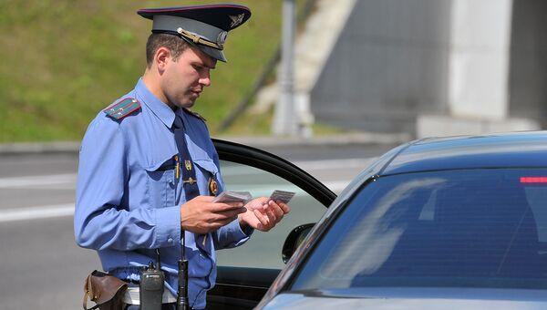 Сотрудник ГИБДД проверяет документы у водителя на посту ДПС. Архивное фото