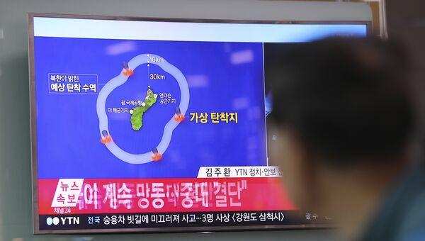 Мужчина смотрит новостную программу, в которой сообщается о планах Северной Кореи по запуску ракет в воды вблизи острова Гуам, в Южной Корее. 15 августа 2017 года
