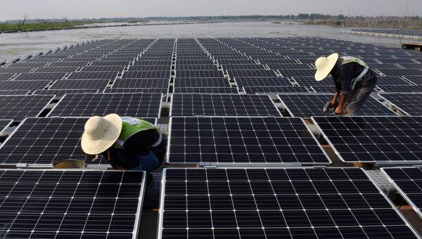 Рабочие на плавучей солнечной электростанции в Китае. Архивное фото